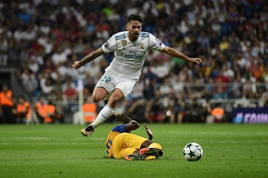Real Madrid's midfielder from Spain Isco jumps to avoid an APOEL's player during the UEFA Champions League football match Real Madrid CF vs APOEL FC at the Santiago Bernabeu stadium in Madrid on Sept 13, 2017.