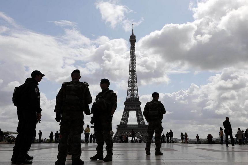 Policemen and French soldiers from the Sentinelle operation patrol on the trocadero Square on Sept 12, 2017, in Paris.