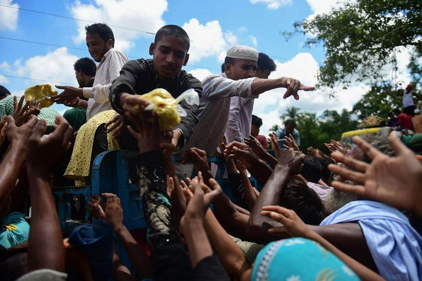 Rohingya refugees from Myanmar gather around a truck delivering food aid in Ukhia on Sept 14, 2017.