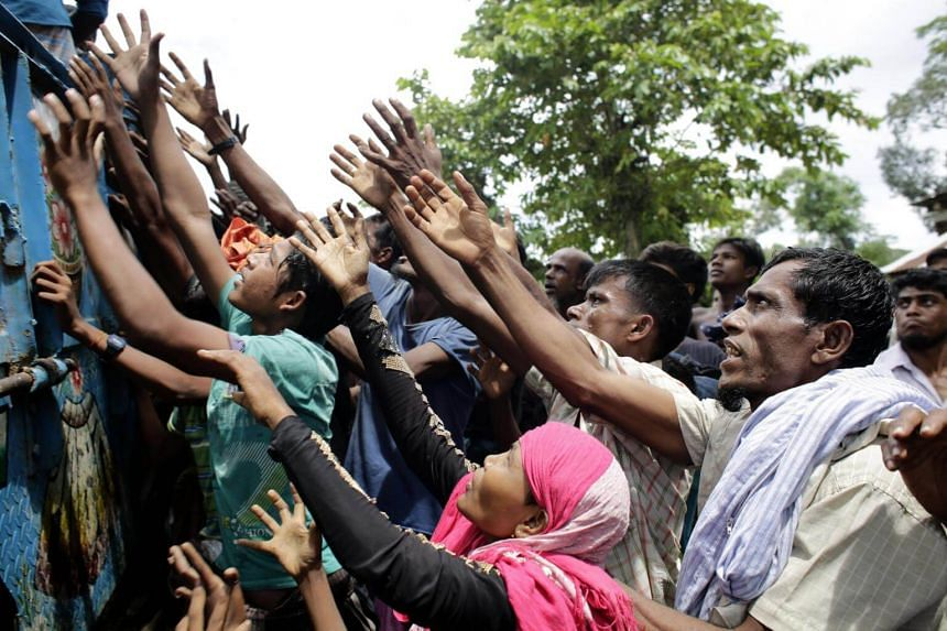 Rohingya Refugees raise their hands to get relief in Ukhiya, Bangladesh on Sept 14, 2017. Many of the Rohingya fleeing the violence in Myanmar had travelled by boat to find refuge in neighbouring Bangladesh.