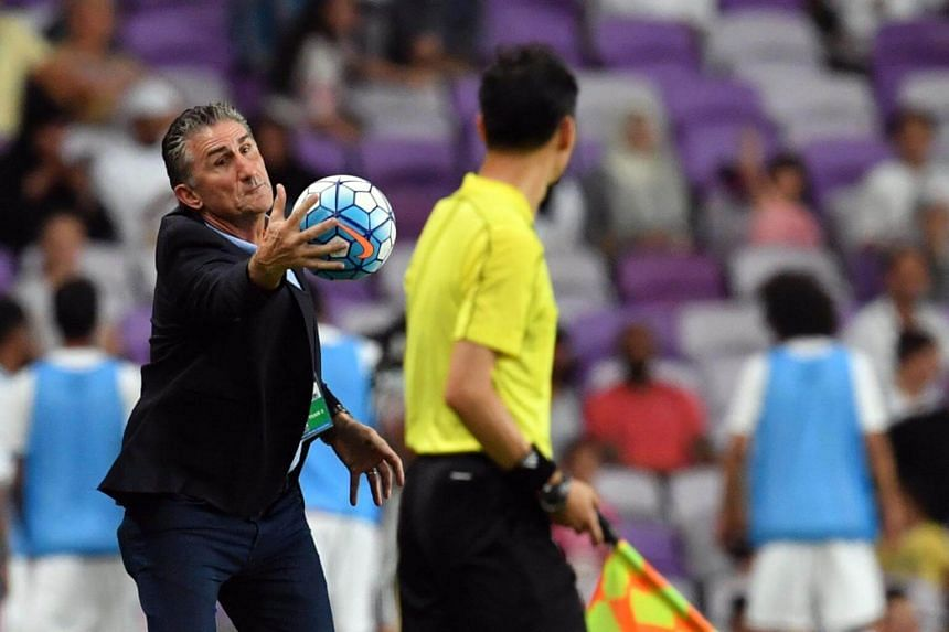 UAE's Argentine coach Edgardo Bauza (left) catches the ball during the 2018 FIFA World Cup qualifier football match between UAE and Saudi Arabia at the Hazza Bin Zayed Stadium in Al-Ain on Aug 29, 2017.