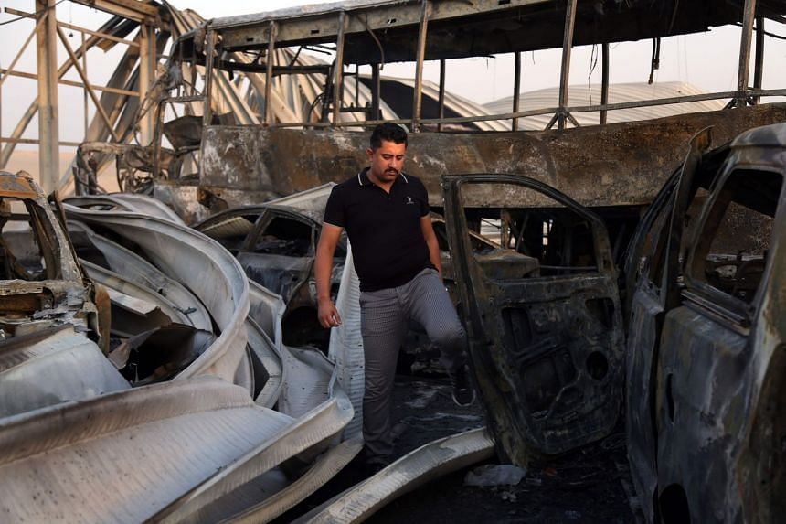 An Iraqi man looks at the damage after gunmen and suicide car bombers killed dozens of people in two assaults claimed by ISIS.