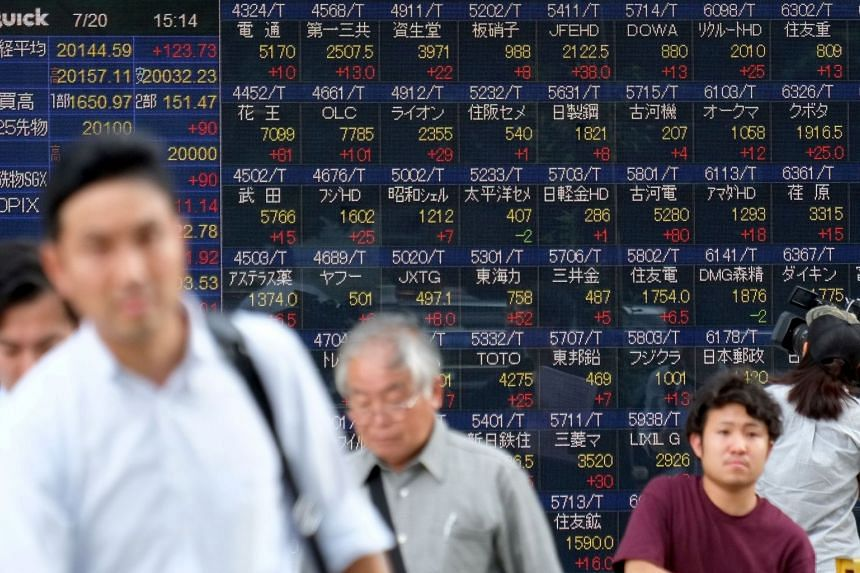 Pedestrians walk in front of a stock quotation board of the Tokyo Stock Exchange in front of a securities company in Tokyo.