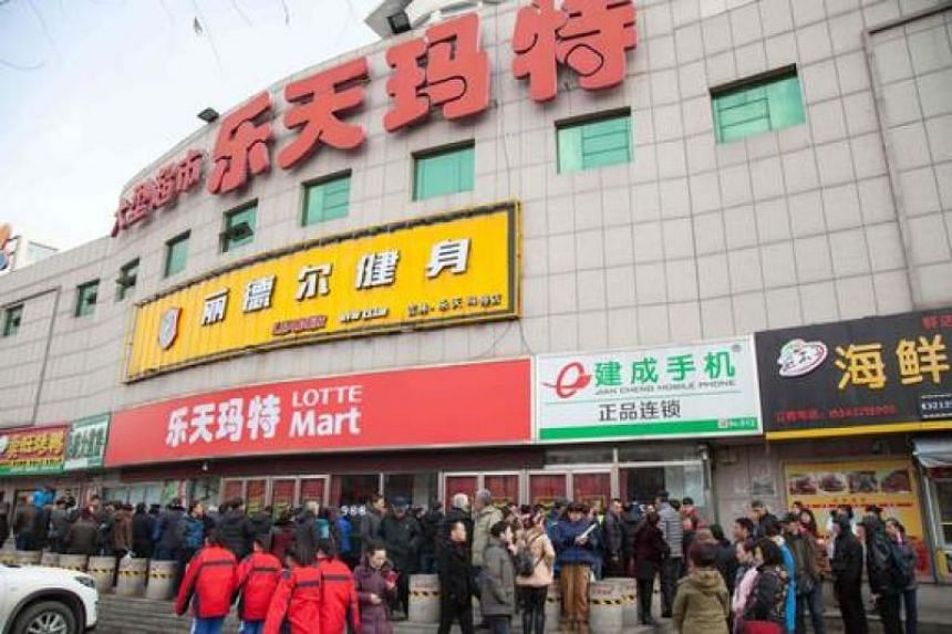 People stand outside a closed Lotte store in Jilin, northeast China's Jilin province, on March 9, 2017.