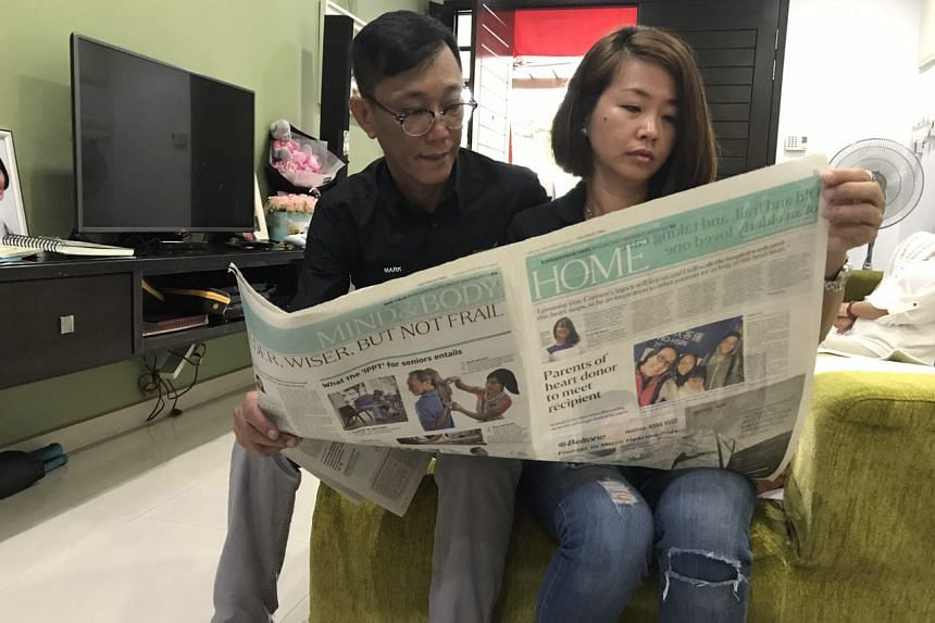 Carmen's parents holding up a copy of The Straits Times report on the reunion with Carmen's heart recipient.
