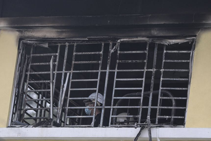A Fire and Rescue Department officer inspecting one of the school's rooms. Many students were trapped inside the burning building by window grilles on the third floor.