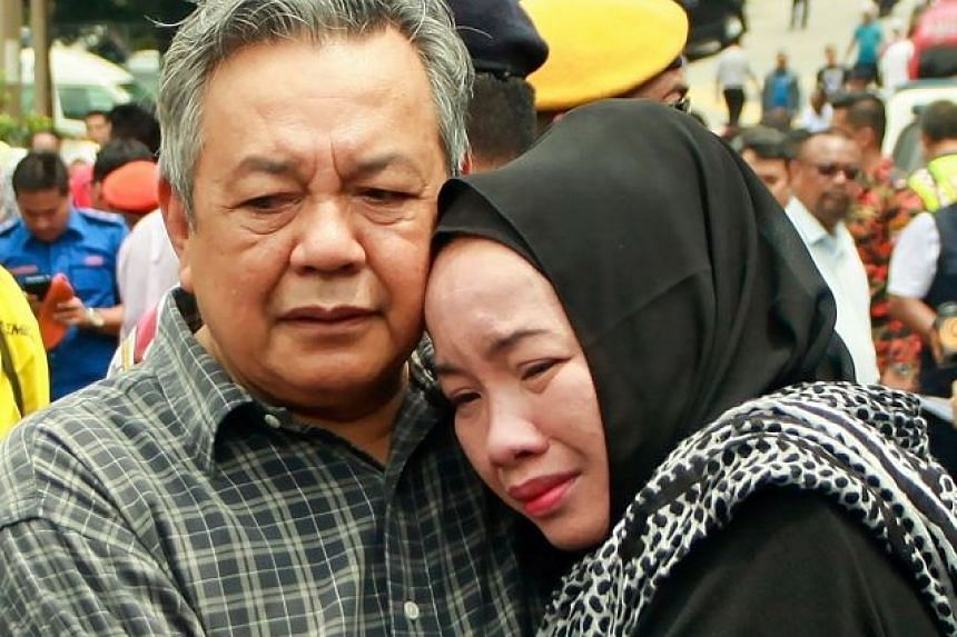 Nik Azlan Nik Abdul Kadir and his wife, who lost their child, grieving outside the school.