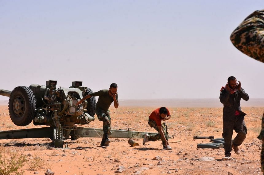 Syrian government forces fire artillery shells as they advance against ISIS militants near Deir Ezzor,  Sept 7, 2017.