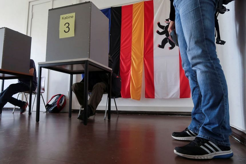 People sit in a voting cabin to cast their vote in an advanced postal ballot for the upcoming general elections at Steglitz-Zehlendorf district postal ballot polling station, in Berlin, Germany, on Sept 15, 2017.