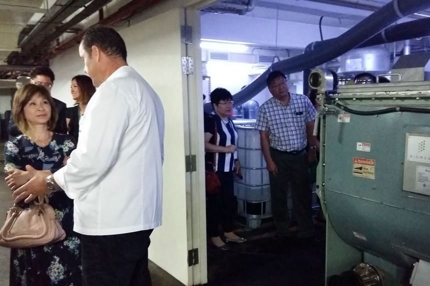 Dr Amy Khor (left) speaks to Chef Lucas Glanville, director of culinary operations at Grand Hyatt Singapore, beside the Biomax Thermophilic Digester machine which recycles food waste for the hotel.