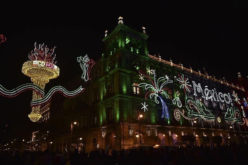 The Mexican Municipality building is illuminated on the eve of the celebration of the 207th anniversary of Mexico's Independence Day at the Zocalo Square in Mexico City yesterday. The anniversary marks a rebel priest's call to arms that inspired an u