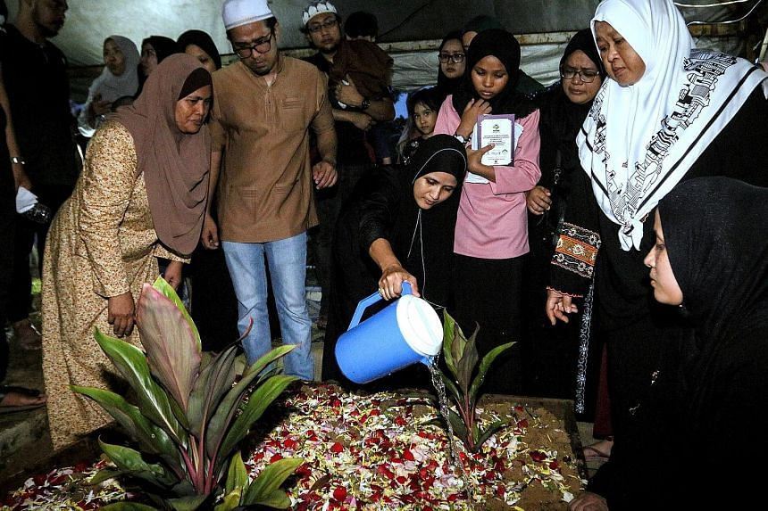 Ms Norazlin Abd Aziz watering the grave of her son Muhammad Afiq Haqiemie Hairulizwan, 11, one of the victims of the fire at Darul Quran Ittifaqiyah tahfiz school, after he was buried at the Jalan Ampang Muslim cemetery yesterday. Ms Siti Halijah, an