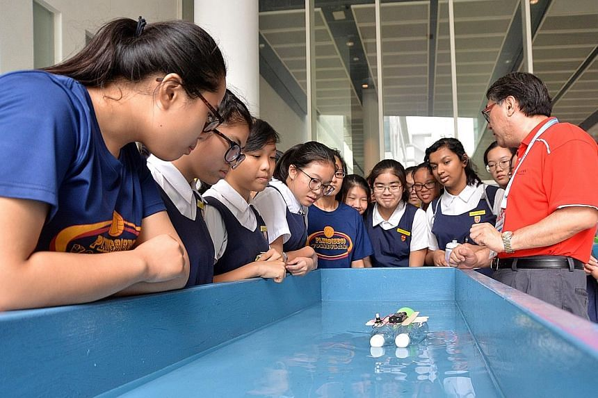 Students from Paya Lebar Methodist Girls' School attending an electrical boat-building workshop conducted by Ngee Ann Polytechnic course manager Zhou Yili.