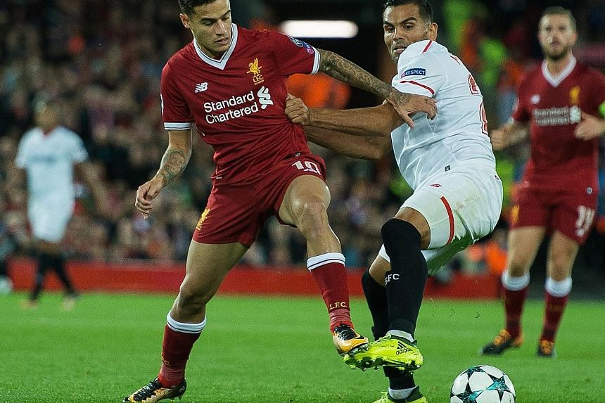 Reds playmaker Philippe Coutinho tussling with Sevilla's Gabriel Mercado during their Champions League Group E tie at Anfield. The Brazilian, who handed in a transfer request, saw his dream move to Barca collapse but will now knuckle down to win back