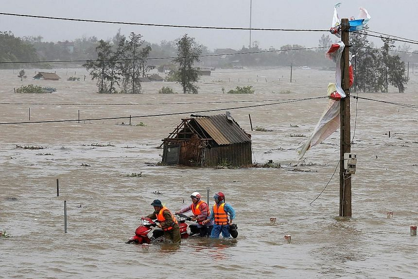 People in Ha Tinh province wading through flood waters yesterday. Vietnam has been hit by severe weather several times this year, with about 140 people dead or missing in natural disasters since January.