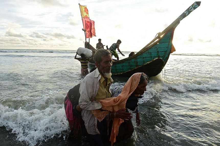 Rohingya refugees disembarking from a Bangladeshi boat on the shores of the Naf river in Teknaf, after crossing from Myanmar on Thursday.