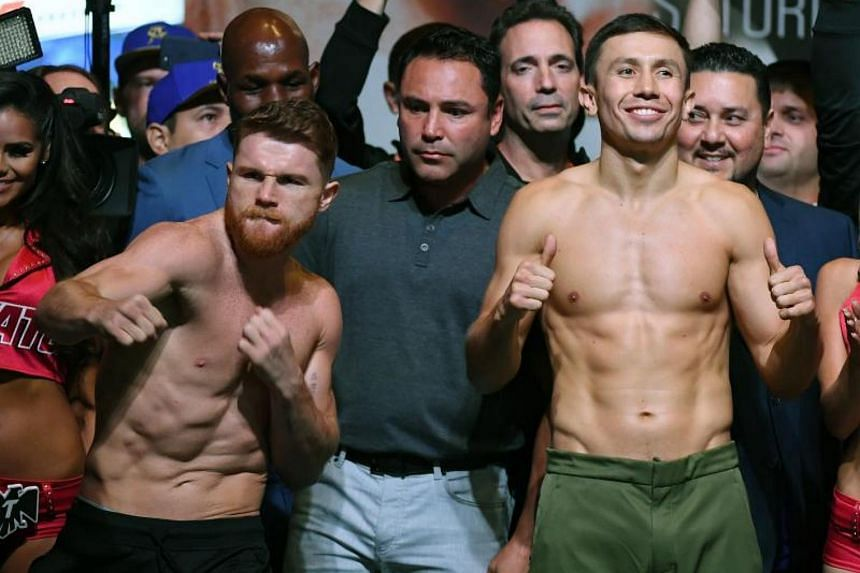 Golden Boy Promotions chairman and CEO Oscar de la Hoya (centre) looks on, as Canelo Alvarez (left) and WBC, WBA and IBF middleweight champion Gennady Golovkin pose during their official weigh-in at MGM Grand Garden Arena on Sept 15, 2017 in Las Vega