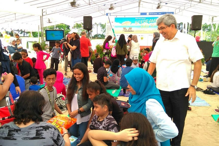 Minister for Communications and Information Yaacob Ibrahim mingling with families as they compete to build the highest sandcastle tower during a carnival to celebrate Stepfamily Day.