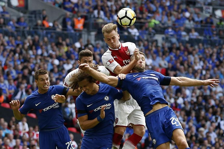 Arsenal's English defender Rob Holding (centre) goes up for a header during the English FA Community Shield football match between Arsenal and Chelsea, on Aug 6, 2017.