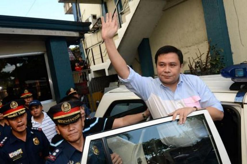 """Philippine Senator Jose """"Jinggoy"""" Estrada waving to supporters as he gets into a police car on his way to a detention center after surrendering to authorities at police headquarters in Manila on June 23, 2014."""