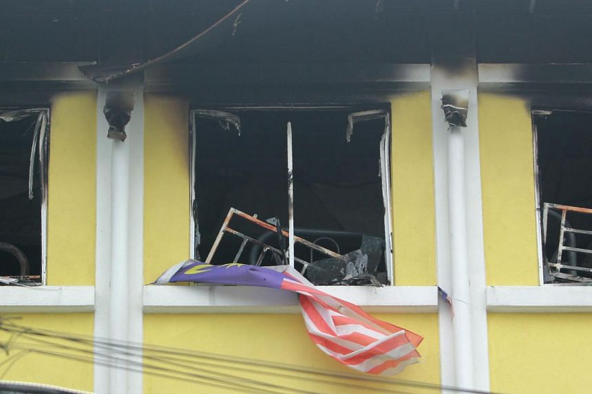 A Malaysian national flag flutters outside burnt windows of the Darul Quran Ittifaqiyah religious school in Kuala Lumpur on Sept 14, 2017.