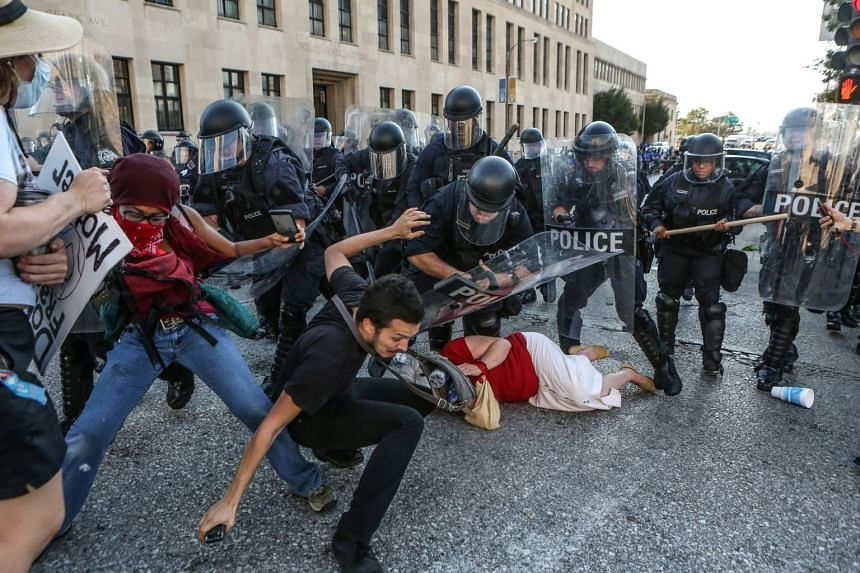 Protesters fall as they are pushed back by police in riot gear, Sept 15, 2017.