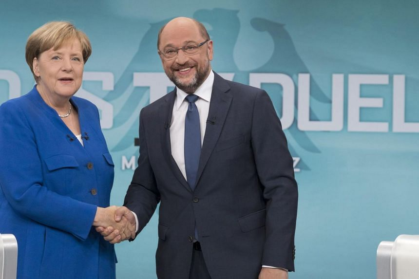 German chancellor Angela Merkel and Martin Schulz, leader of Germany's social democratic SPD party shaking hands before a televised debate in Berlin on Sept 3, 2017.