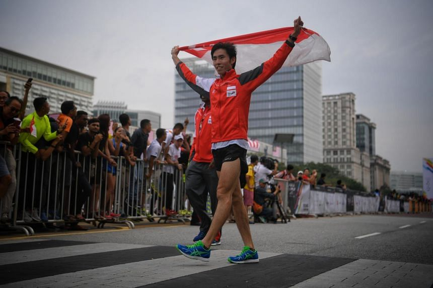 Soh Rui Yong raises the Singaporean flag after finishing first during the marathon in Putrajaya on Aug 19, 2017.