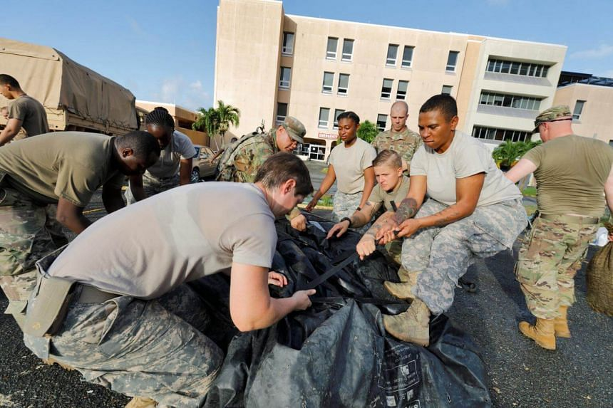 Soldiers securing a portable tent while breaking down a field hospital, during an evacuation in advance of Hurricane Maria, in Charlotte Amalie on Sept 17, 2017.