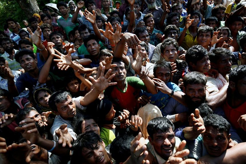 Rohingya refugees stretch their hands for relief supplies given by local people in Cox's Bazar, Bangladesh on Sept 16, 2017.