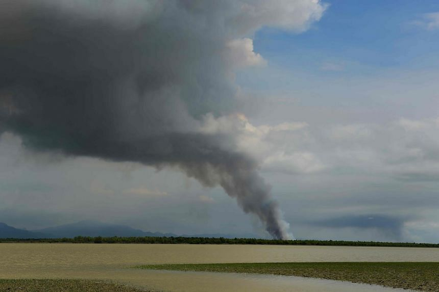 Smoke is seen billowing in an area inland in Myanmar's Rakhine state as seen from the Bangladeshi shore of the Naf river on Sept 14, 2017.