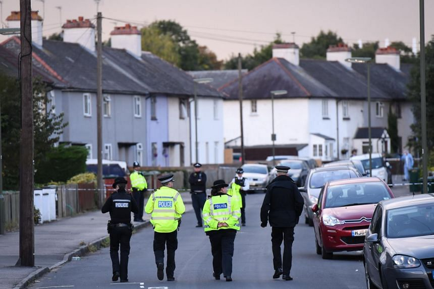 Police stand guard during a police raid in Sunbury, Surrey, near London on Sept 16, 2017.
