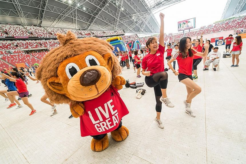 Great Eastern Women's Run participants getting into the groove in a mass Zumba session at the National Stadium yesterday. They were among the 18,000 people taking part in the Super Warrior-themed Sports Hub Community Play Day. This was the second fri