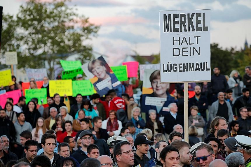 "A poster reading ""Merkel hold your lying mouth"" at one of German Chancellor Angela Merkel's election rallies reflects the anger of voters ahead of next week's general election."