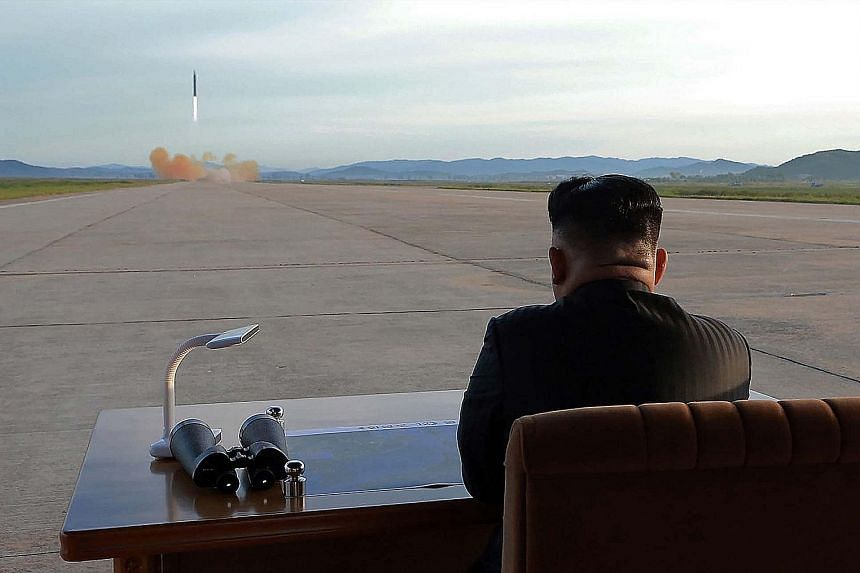 An undated picture released by North Korea's official Korean Central News Agency yesterday showing Mr Kim Jong Un inspecting a launch drill of the Hwasong-12 missile at an undisclosed location.