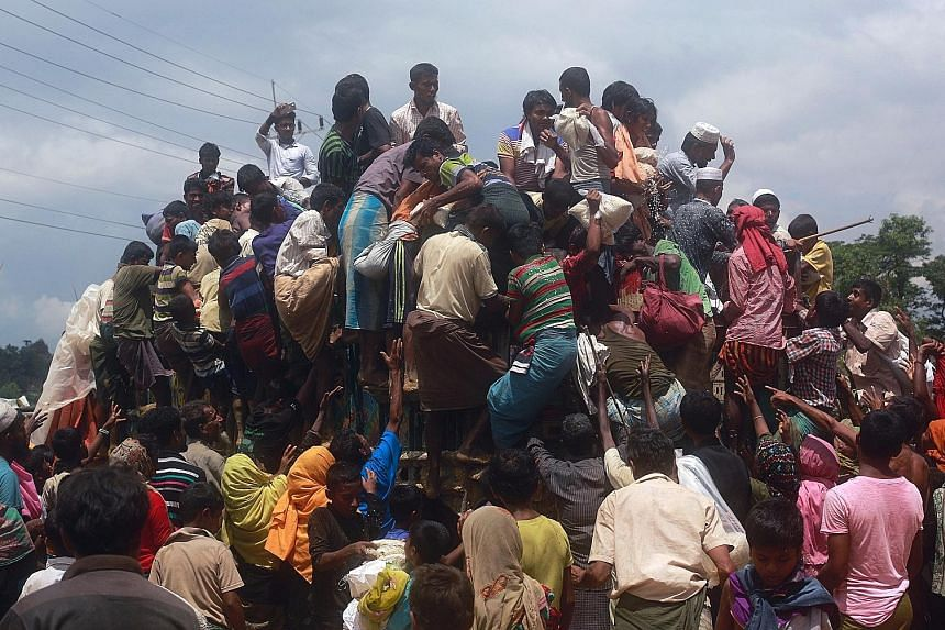 Rohingya refugees climbing a truck to receive aid from local organisations at the Balukhali Makeshift Refugee Camp in Cox's Bazar, Bangladesh, last Thursday. While local volunteers have been helping with handouts for refugees, the chaotic distributio