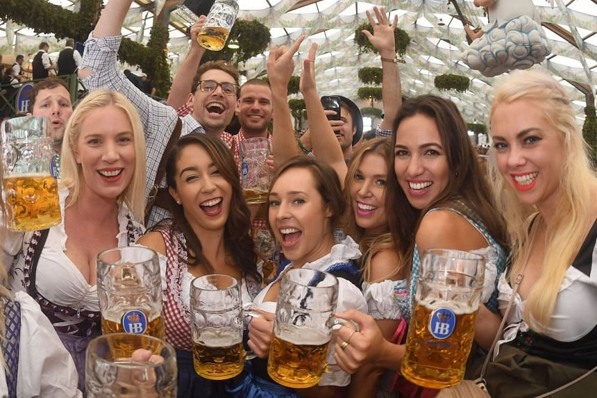 People drink the first mugs of beer after the official opening of the 184th Oktoberfest.