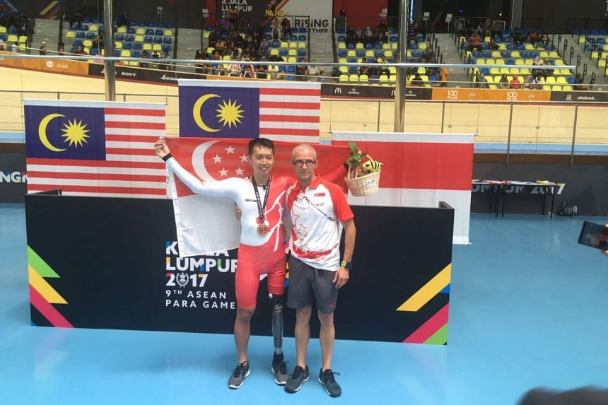 Tan Hun Boon (left) with national para-cycling coach Christian Stauffer after the medal ceremony.