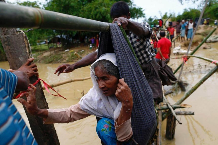 A Rohingya refugee woman is carried in a sling, through a swollen water stream in Cox's Bazar, Bangladesh, on Sept 18, 2017.