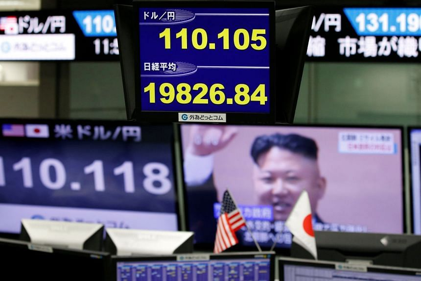Monitors showing TV news on North Korea's missile launch (right), the Japanese yen's exchange rate against the US dollar and Japan's Niikei share average (bottom of blue screen) are seen at a foreign exchange trading company in Tokyo, Japan, on Sept