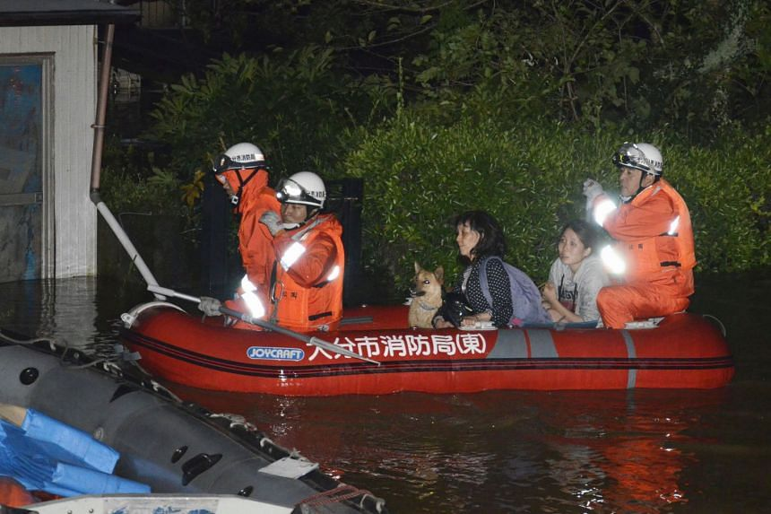 Local residents are evacuated by boat from an inundated house due to a heavy rain triggered by Typhoon Talim, in Oita, southern Japan, in this photo taken by Kyodo, on Sept 17, 2017.