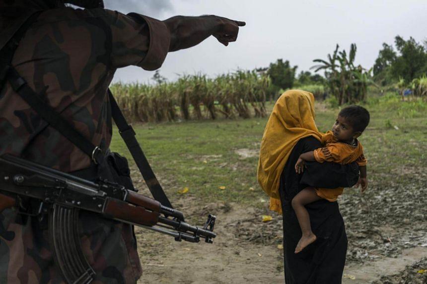 A Bangladeshi border guard sends a Rohingya woman and child back to their makeshift camp along the border with Myanmar near Gundum, Bangladesh, on Aug 31, 2017.