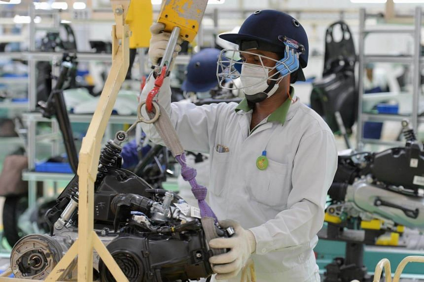An employee mounts the engine of a Honda Activa scooter into the chassis at the 4th assembly line after its inauguration at the Honda Motorcycle & Scooter India Pvt. Ltd.