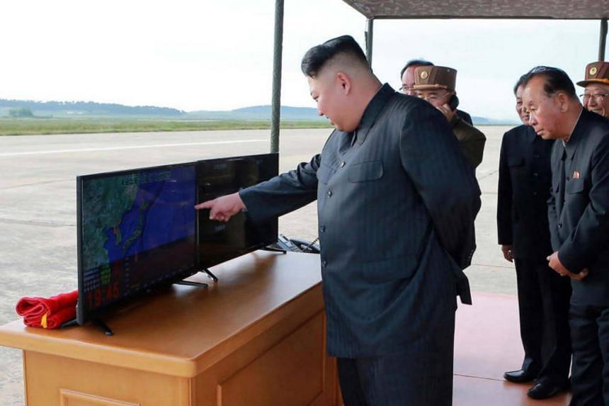 North Korean leader Kim Jong Un (left) inspecting a launching drill of the medium-and-long range strategic ballistic rocket Hwasong-12 at an undisclosed location on Sept 16, 2017.