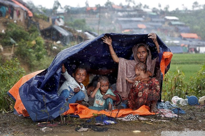 Rohingya refugees taking shelter from the rain in a camp in Cox's Bazar, Bangladesh, yesterday. More than 400,000 members of Myanmar's Rohingya Muslim minority have fled the country's western Rakhine state to Bangladesh in an effort to escape a milit