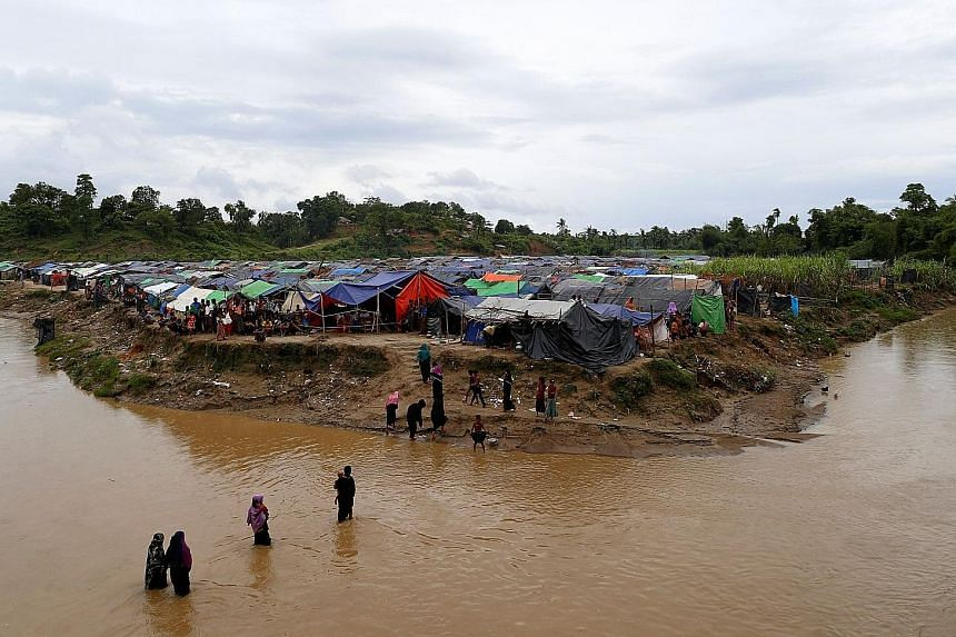 Rohingya refugees crossing a stream to reach their temporary shelters in the no-man's-land between Bangladesh and Myanmar on Sept 9. For now, they have regular food deliveries and access to clean water and medicines, thanks to the local commander of