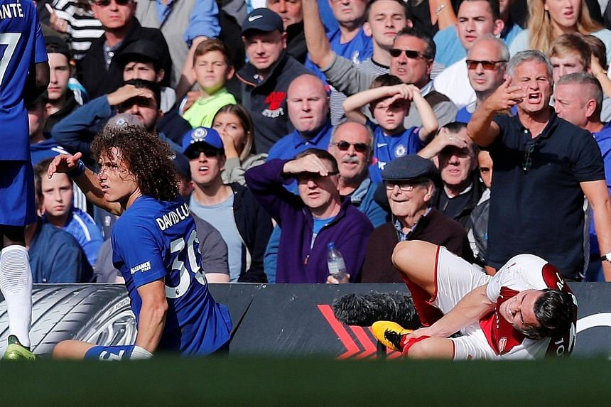 Arsenal's Sead Kolasinac clutches his left shin after a challenge by Chelsea centre-back David Luiz. The Brazilian was sent off in the 87th minute and Arsenal had little time to capitalise on their numerical advantage.