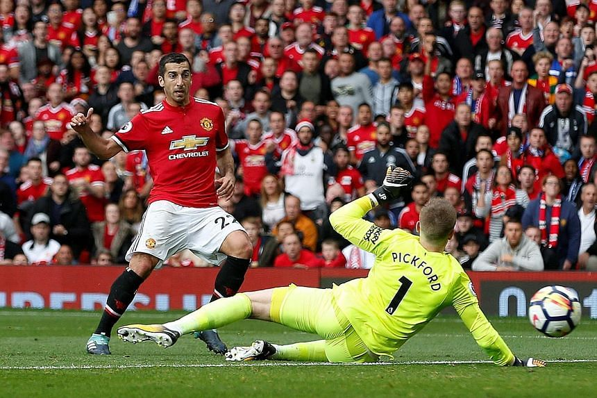Manchester United's Henrikh Mkhitaryan slots home past Everton goalkeeper Jordan Pickford for their second goal. The Red Devils went on to net two more goals in the final two minutes.