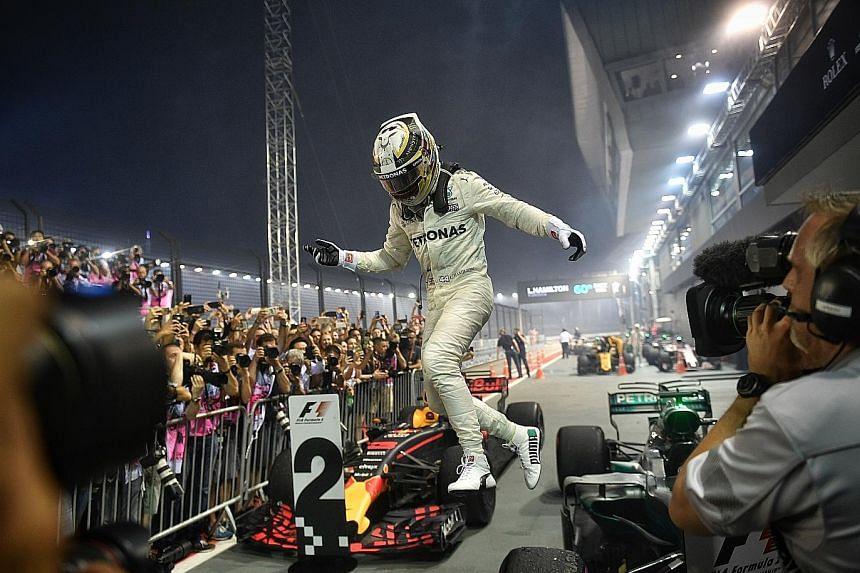 An ecstatic Lewis Hamilton jumping off his Mercedes after winning a third Singapore Grand Prix last night, to take a commanding lead over Ferrari's Sebastian Vettel.
