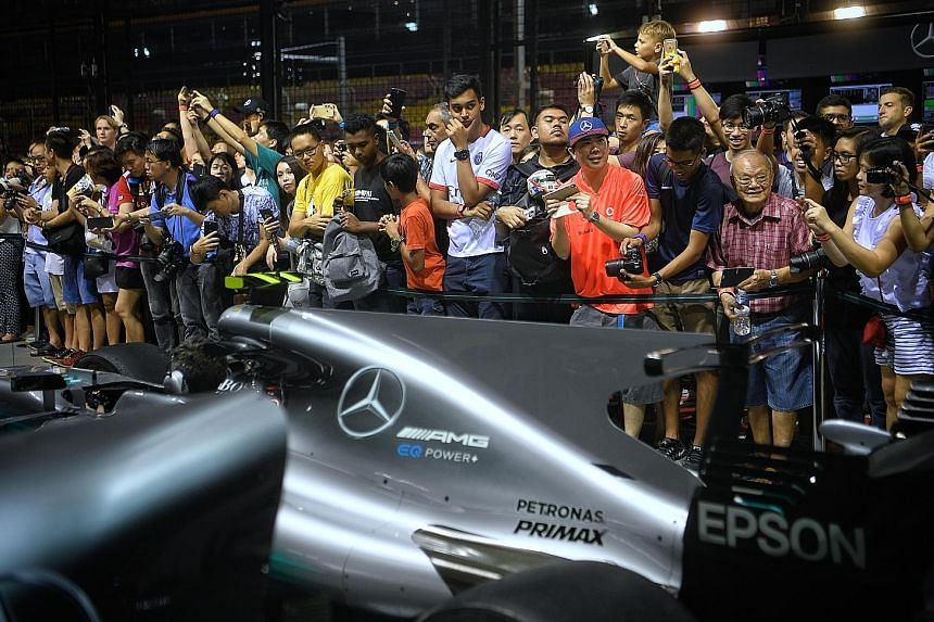Fans get up close to watch the Mercedes pit crew in action during the Thursday Pit Lane Experience at the Marina Bay Street Circuit on Sept 14. Giving fans an enhanced experience is a pivotal strategy for the sport's new American owners.